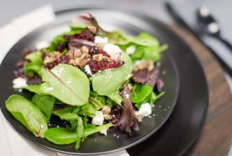 Plated salad with greens, nuts, and cranberries