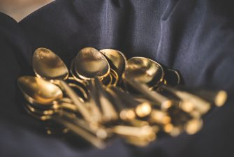 Basket of shiny spoons over a blue cloth