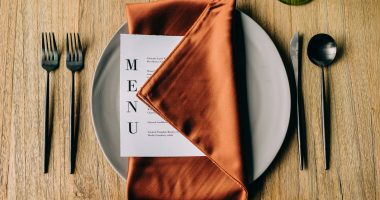 place setting with a menu tucked into an orange napkin