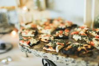 Array of various flatbreads on granite buffet display with fresh tomato and herbs