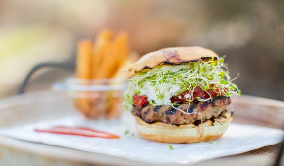 close up of burger with sprouts, fries in background